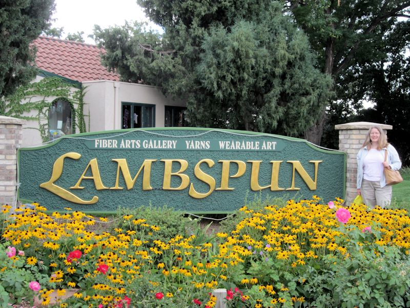 Large sign saying Lambspun, with yellow and red flowers in front. A woman stands beside the sign.