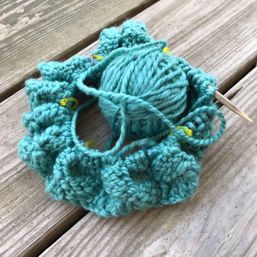 Ball of handspun yarn and handknit cowl in progress, on wooden circular needles.